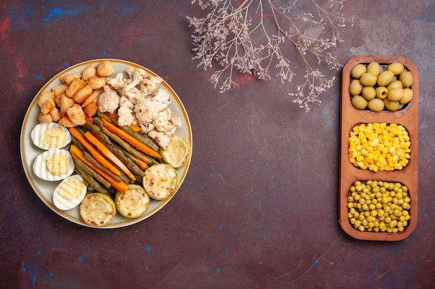 Vista dall'alto di verdure cotte con farina di uova e fagioli su uno spazio buio
