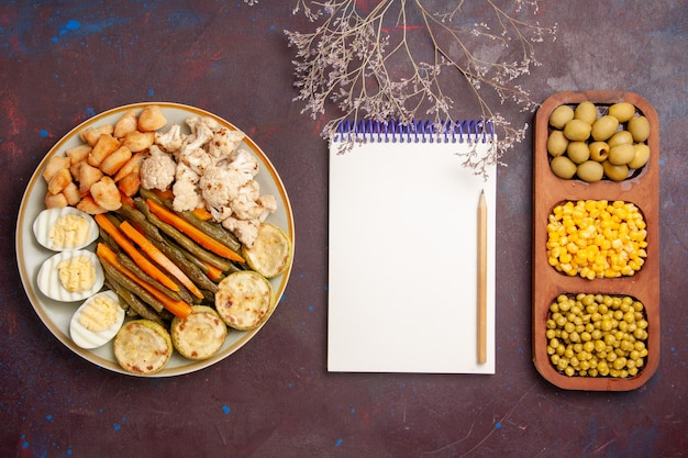 Vista dall'alto di verdure cotte con fagioli di farina di uova e blocco note su uno spazio buio