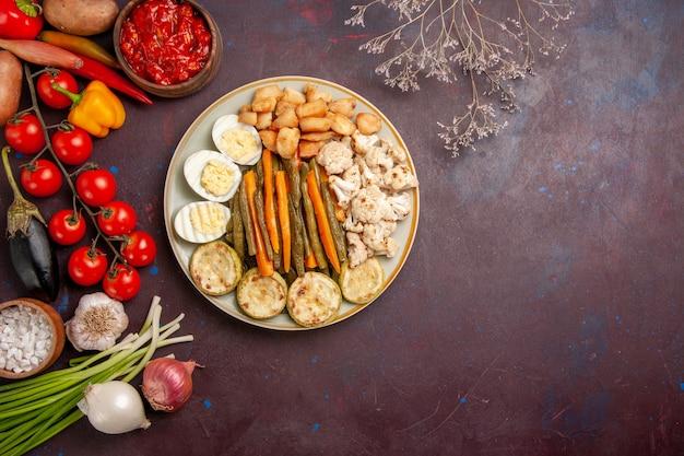Vista dall'alto di verdure cotte con farina di uova e verdure fresche sulla scrivania scura