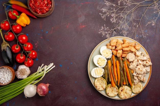 Vista dall'alto di verdure cotte con farina di uova e verdure fresche su uno spazio buio