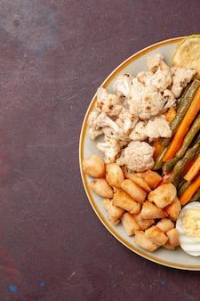 濃い紫色の空間で卵の食事と一緒に調理された野菜の上面図