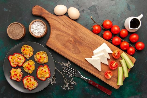 Vista dall'alto di verdure cotte con uova crude e pomodori freschi sulla superficie scura