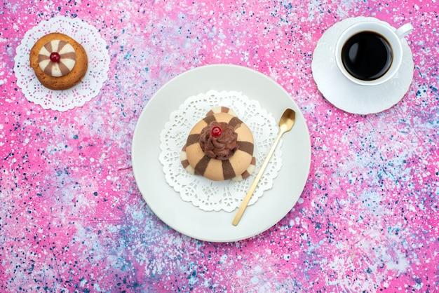 トップビューのクッキーと色付きの背景にコーヒーのカップとケーキ
