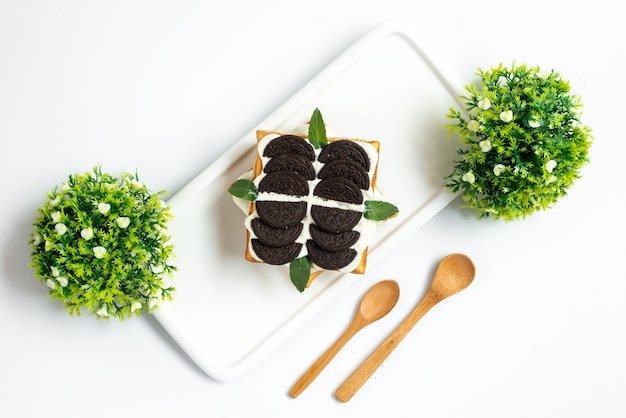 A top view cookie cake chocolate cookie based delicious cake with custard inside white desk along with plants and wooden spoons cake sweet sugar