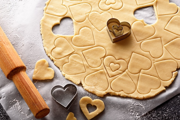 Top view of cookie dough with cut out shapes in the form of heart on white parchment paper for the valentines day