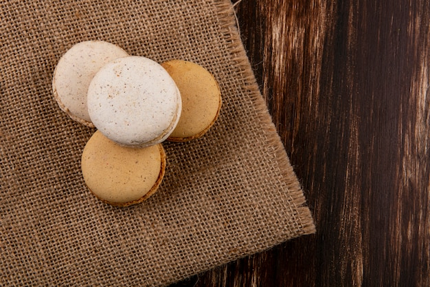 Top view of cookie sandwiches on sackcloth and wooden background with copy space