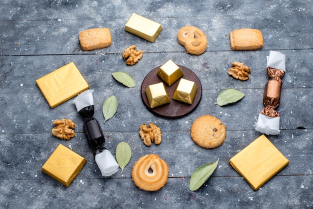 Vista dall'alto di biscotti e noci insieme a torta al cioccolato su grigio, zucchero dolce al cioccolato biscotto