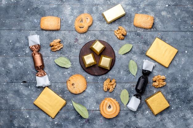 Vista dall'alto di biscotti e noci insieme a torta al cioccolato su grigio, biscotto biscotto dolce al cioccolato