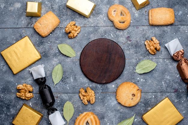 Vista dall'alto di biscotti e noci insieme a torta al cioccolato su grigio, biscotto al cioccolato