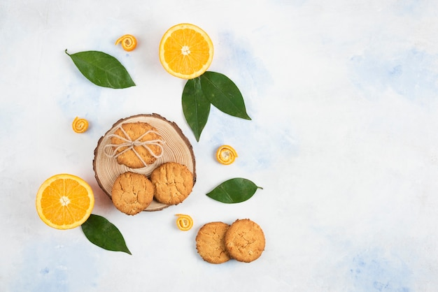 Top view of cookie on wooden board and half cut orange with leaves over white surface.