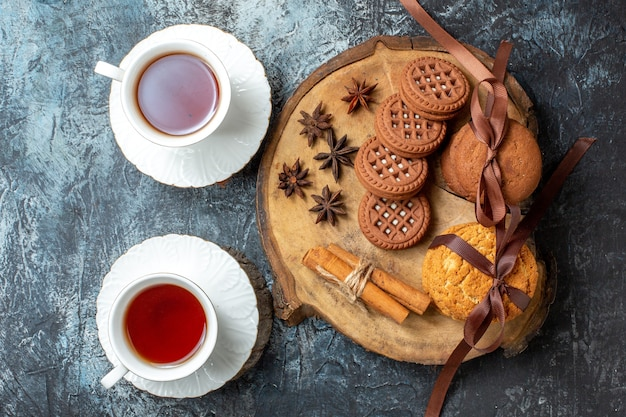 Вид сверху печенье и бисквиты, анисы, палочки корицы на круглой деревянной доске, две чашки чая на темном столе