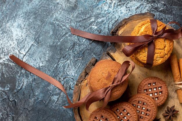 Вид сверху печенье и бисквиты, анисы, палочки корицы на деревянной доске на темном месте для копирования стола