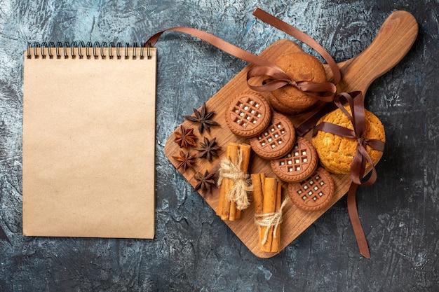 Вид сверху печенье и бисквиты с анисом, палочки корицы на деревянной сервировочной доске, блокнот на темном столе
