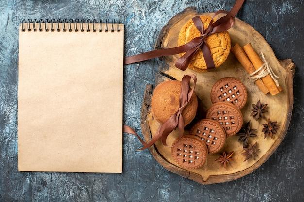 Вид сверху печенье и бисквиты, палочки корицы, перевязанные веревкой, на деревянной доске блокнота на темном столе