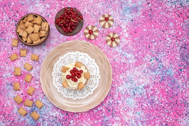 紫色の背景のクッキービスケット色のフルーツにクランベリーと一緒にトップビュークッキーとケーキ