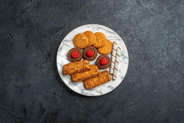 灰色のスペースのプレート内のトップビューのクッキーとケーキ