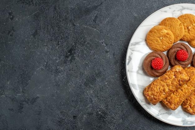 Вид сверху печенье и торты внутри тарелки на темно-сером пространстве