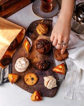 光の表面に茶色の木製の机の上のクッキーとケーキのトップビュー