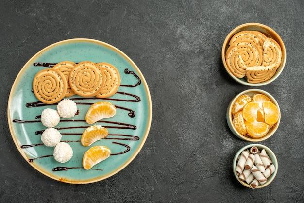 灰色のテーブルの甘いビスケットクッキーにみかんのトップビュークッキーとキャンディー