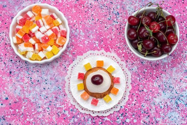 Вид сверху печенье и вишня вместе с мармеладом на цветном фоне сладкого сахарного торта