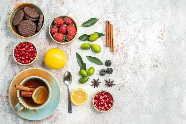 Vista dall'alto biscotti e bacche biscotti appetitosi fragole cucchiaio una tazza di tè agrumi cannella sul tavolo