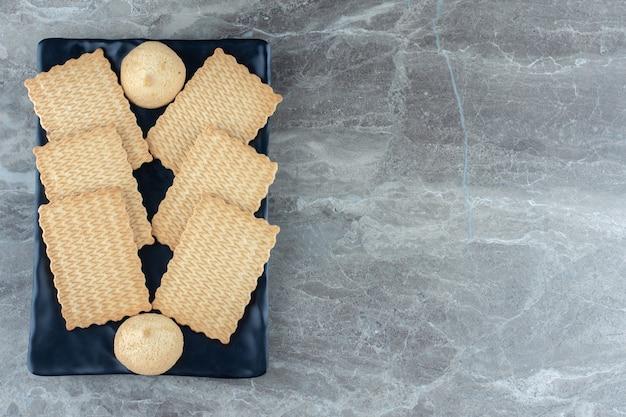 Vista dall'alto di biscotti in piatto di ceramica nera.