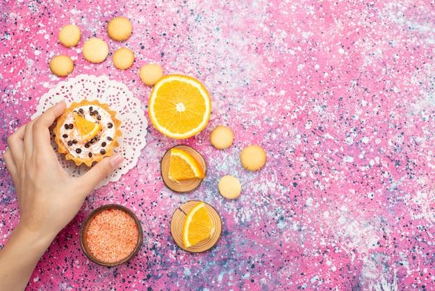 Vista dall'alto biscotti e torta con fette d'arancia sulla superficie colorata biscotto biscotto torta di frutta zucchero dolce