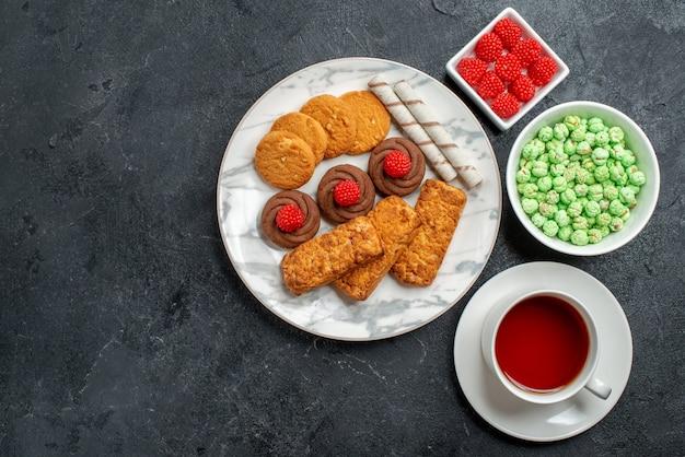 Biscotti e torte di vista dall'alto con una tazza di tè su uno spazio grigio