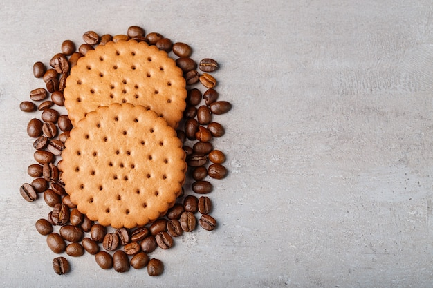 Top view cookies on coffee beans on a light grey background