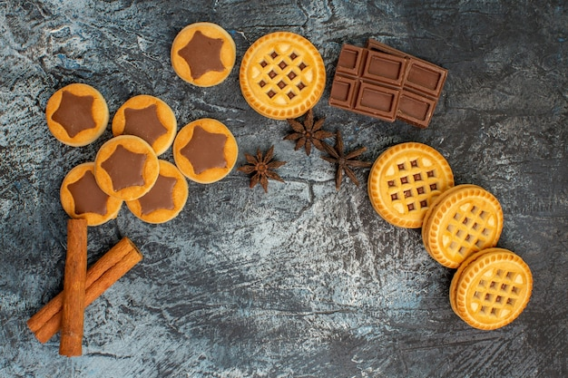 Top view of cookies of crescent shaped layout with cinnamon and chocolate on grey background