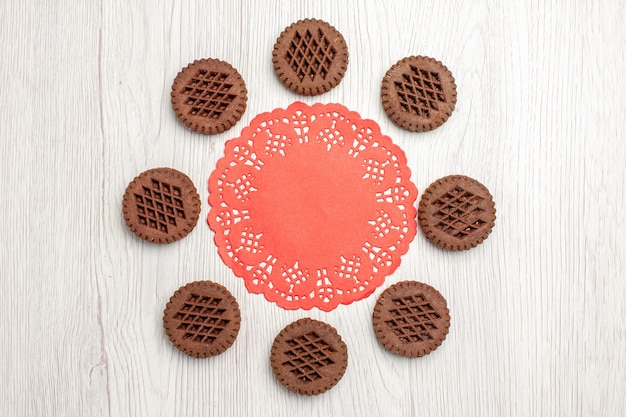 Top view cookies and the red oval lace doily on the white wooden table