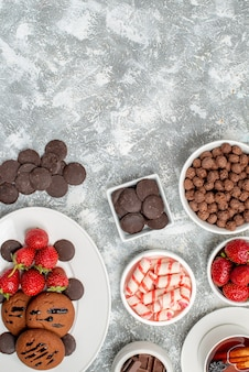 上面図クッキーイチゴと丸いチョコレート、キャンディーイチゴチョコレートシリアルと灰色がかった白いテーブルの下部にお茶を入れた楕円形のプレートボウル