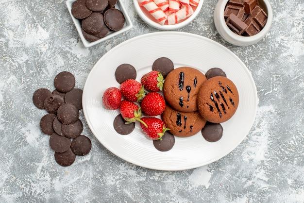 Vista dall'alto biscotti fragole e cioccolatini rotondi sul piatto ovale ciotole con cioccolatini caramelle e cioccolatini amari rotondi sul tavolo grigio-bianco