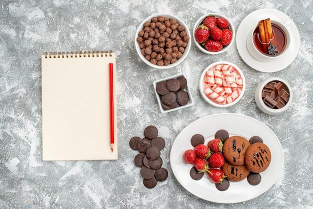 Vista dall'alto biscotti fragole e cioccolatini rotondi sul piatto ovale ciotole con caramelle fragole cioccolatini cereali una tazza di tè e matita taccuino sul tavolo grigio-bianco