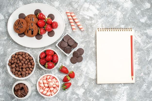Vista dall'alto biscotti fragole e cioccolatini rotondi sul piatto ovale ciotole con caramelle fragole cioccolatini cereali e un taccuino con matita sul tavolo grigio-bianco