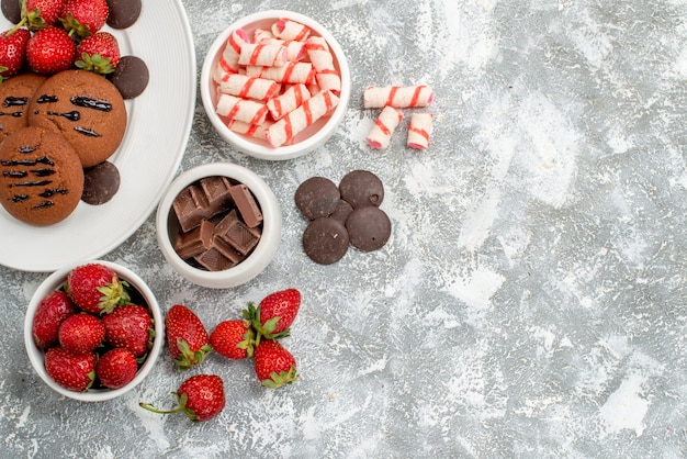 Top view cookies strawberries and round chocolates on the white oval plate bowls of candies strawberries chocolates at the top left of the grey-white table