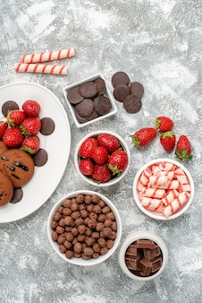 Top view cookies strawberries and round chocolates on the white oval plate bowls with candies strawberries chocolates cereals on the grey-white table