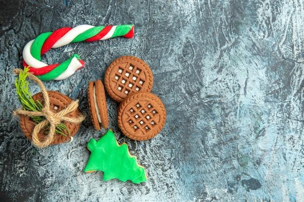 Biscotti di vista superiore legati con caramelle di natale dei biscotti delle corde sullo spazio grigio della copia di superficie