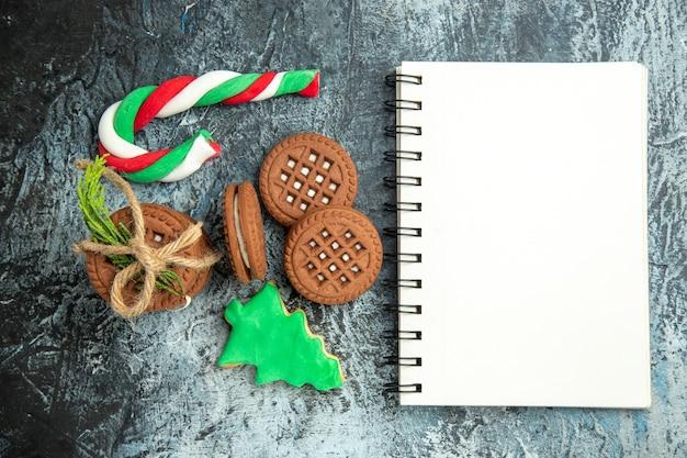 Вид сверху печенье, перевязанное веревками, печенье, рождественские конфеты, блокнот на серой поверхности