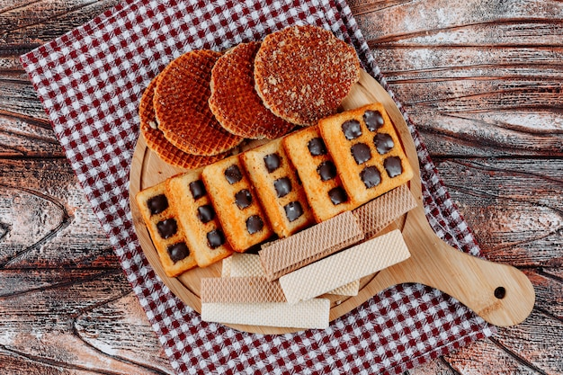 Top view cookies and waffles on cutting board on cloth and wooden background. horizontal