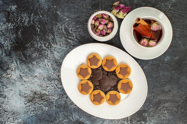 Vista dall'alto di biscotti sul piatto bianco con una tazza di tisana con una ciotola di fiori secchi su fondo grigio