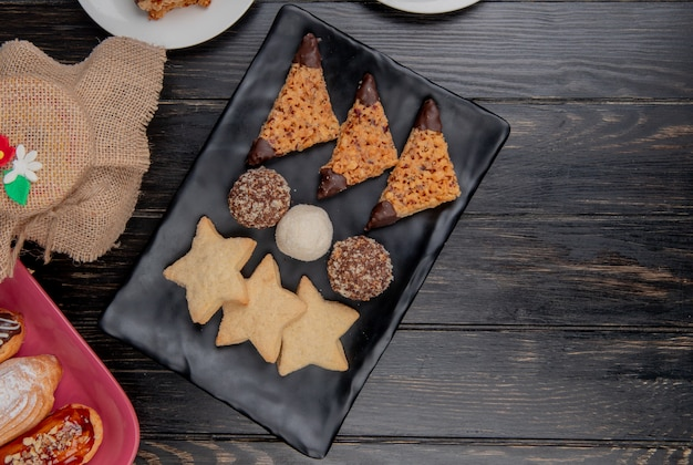 Top view of cookies with cake slices in plate and cakes on wooden background with copy space