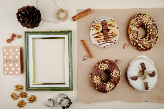 Top view of cookies with cinnamon and walnuts and pinecone and frame on white with copy space