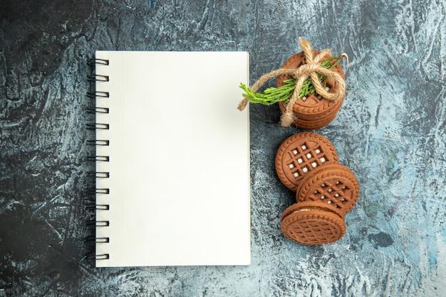 Вид сверху печенье с кремом, перевязанное веревками, блокнот для печенья на серой поверхности