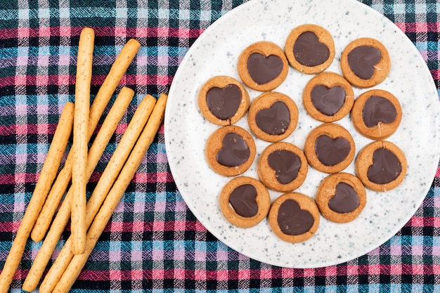 Top view cookies with heart shaped chocolate in plate