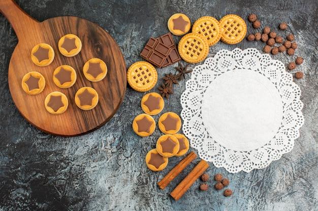 Vista dall'alto di biscotti sul piatto di legno con tanti dolci e un pezzo di pizzo bianco su fondo grigio