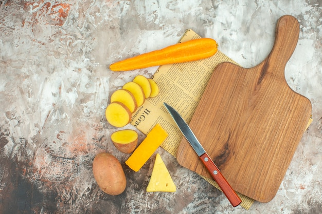 Top view of cooking background with various vegetables and two kinds of cheese knife and wooden cutting board on an old newspaper on mixed color background