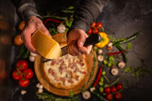 パルメザンチーズ、オリーブオイル、トマト、赤唐辛子のスパイスとハーブを使ってシェフの手でピザを調理する上面図。テキストまたはデザインの暗い背景。ホテルサービスの写真クリップアート。手に焦点を当てる