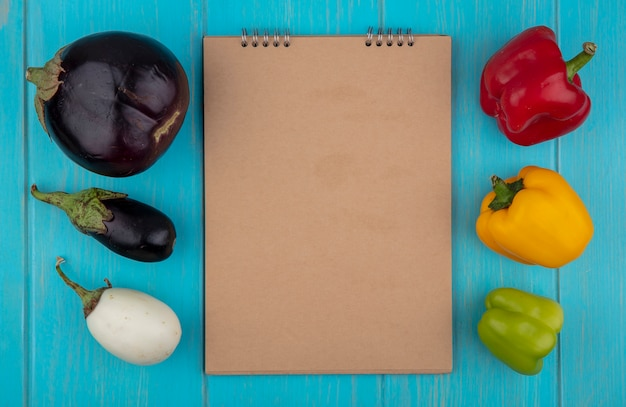 Blocco note beige dello spazio della copia di vista superiore con i peperoni colorati e le melanzane su fondo turchese