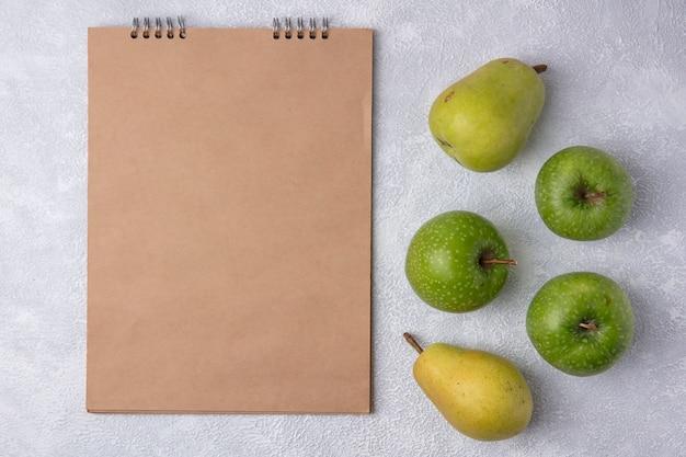 Blocco note beige dello spazio della copia di vista superiore con le mele e le pere verdi su fondo bianco